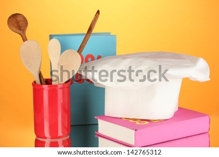 Chef's hat with spoons and cook book on orange background - stock photo