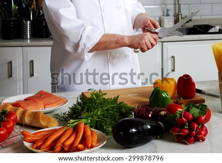 Chef sharpens a knife on a modern stylish kitchen expensive Italian restaurant, to start cooking dinner - stock photo
