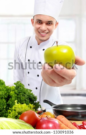 chef showing fresh green apple to camera in the kitchen - stock photo
