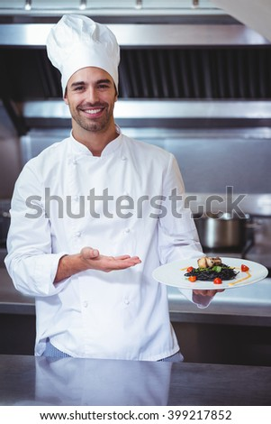 Chef showing his dish in commercial kitchen - stock photo
