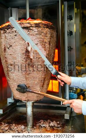 Chef slicing Turkish doner kebab - stock photo