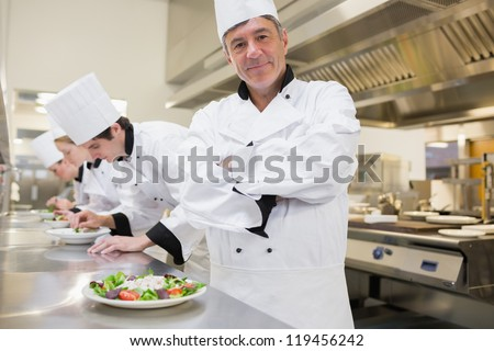 Chef smiling with arms crossed with others preparing salad - stock photo