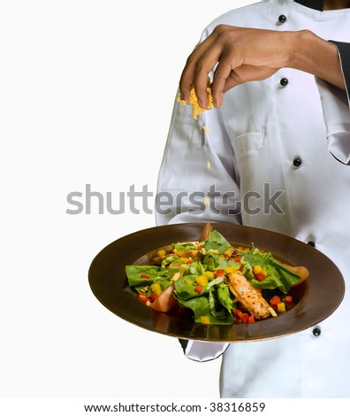 Chef sprinkling cheese on healthy salad isolated on white