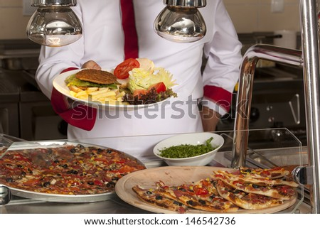 chef standing behind burger,spaghetti and pizza station