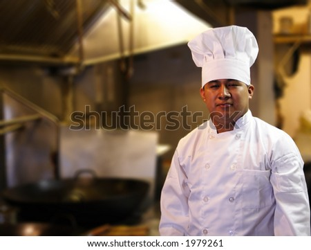 chef standing with blurred kitchen background - stock photo