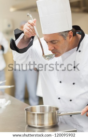 Chef tasting soup while preparing it - stock photo