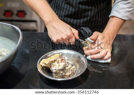 Chef trying to opened fresh oyster in restaurant kitchen - stock photo
