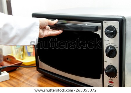 chef using oven for cooking in the kitchen - stock photo