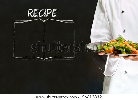 Chef with chalk recipe book on blackboard background - stock photo