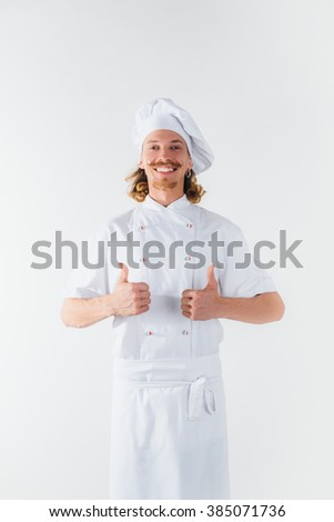 Chef with long red hair in white uniform shows big finger up and smile. Cooking the meal. Vertical portrait of chef