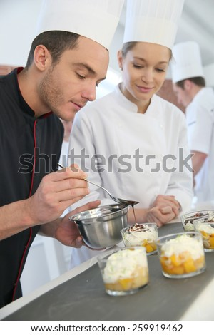 Chef with student in pastry making dessert - stock photo