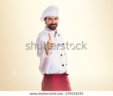 Chef with thumb up over ocher background - stock photo