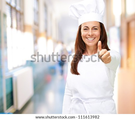 Chef woman showing thumbs up, indoor - stock photo