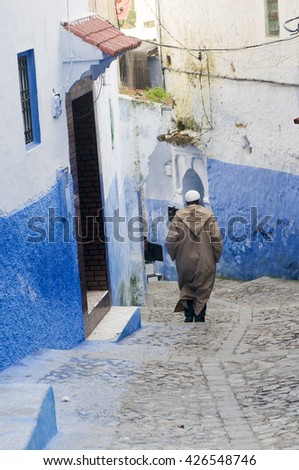 CHEFCHAOUEN, MOROCCO - JANUARY 17, 2010: Unidentified man wearing moroccan robe walking down the blue medina at the ancient town of Chefchaouen in Morocco.  - stock photo