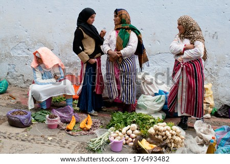 CHEFCHAOUEN, MOROCCO - JANUARY 02: Unidentified smiling women pose for a photo in the souk on January 02, 2014 in Chefchaouen, Morocco. - stock photo