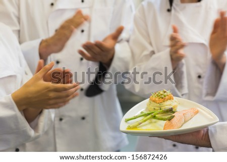 Chefs applauding a salmon dish in commercial kitchen - stock photo