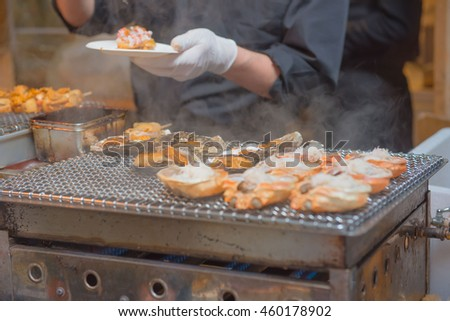 Chefs are cooking grilled shell on the japan market. - stock photo