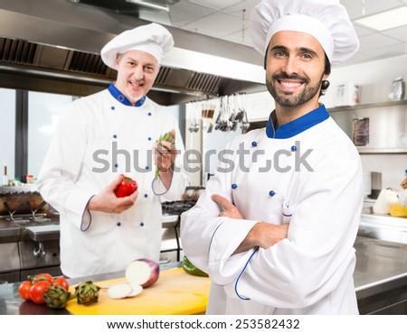Chefs at work in a restaurant kitchen - stock photo