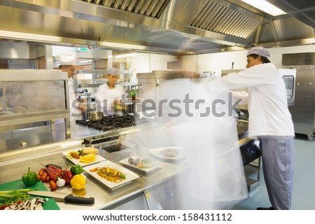 Chefs busy at work in a busy kitchen - stock photo