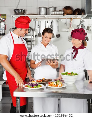 Chefs looking for recipe on a digital computer while cooking at kitchen - stock photo