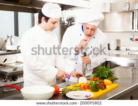 Chefs preparing a dish in a commercial kitchen - stock photo