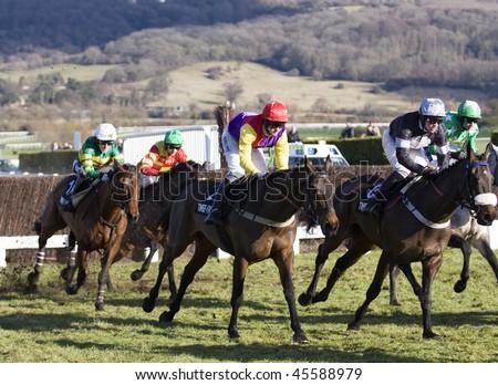 CHELTENHAM, GLOUCS; JAN 30:  Jockeys battle over fences in the second race of festival trials day at Cheltenham Racecourse, UK, January 30, 2010 in Cheltenham, Gloucestershire - stock photo