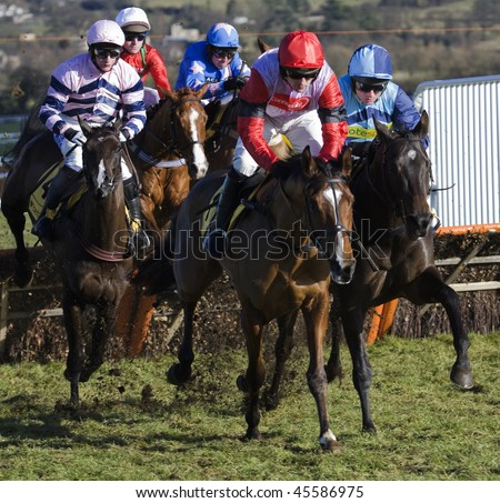 CHELTENHAM, GLOUCS; JAN 30:  Jockeys battle over hurdles in the first race at Cheltenham Racecourse, UK, January 30, 2010 in Cheltenham, Gloucestershire