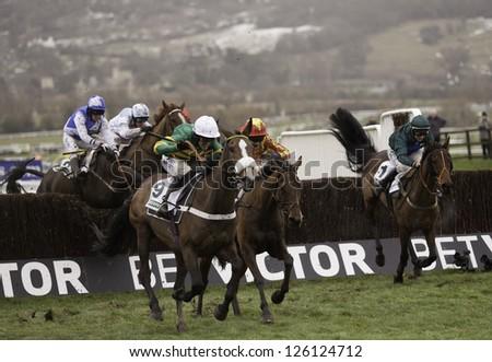 CHELTENHAM, GLOUCS-JANUARY 26: Jockeys take their horses over jumps in the third race at Festival Trials Day, Cheltenham Racecourse, Cheltenham UK on Jan 26, 2013. - stock photo