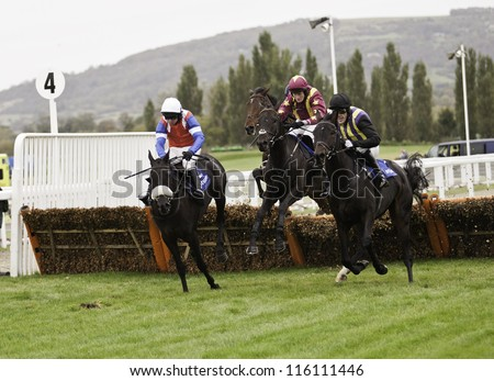 CHELTENHAM, GLOUCS, OCT 19 2012, Jockeys a p mccoy and charlie poste battle over fences in the first race at Cheltenham Racecourse, Cheltenham UK Oct 19 2012 - stock photo
