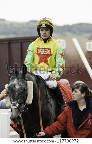 CHELTENHAM, GLOUCS, - OCTOBER 2012: jockey Ruby Walsh returning from the second race with that'lldoboy at Cheltenham Racecourse, cheltenham UK on October 20, 2012 - stock photo