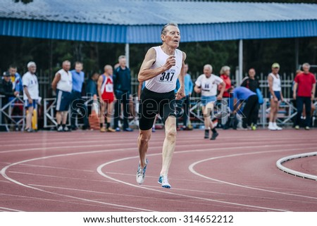 Chelyabinsk, Russia - August 28, 2015:  75 year old man runs 400 meters during championship of Russia on track and field athletics among the elderly, Chelyabinsk, Russia - August 28, 2015 - stock photo