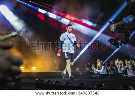 Chelyabinsk, Russia - December 5, 2015: athlete mixed martial arts fighter is catwalk surrounded by fans. fans greet him. light and smoke during Cup of Russia MMA - stock photo