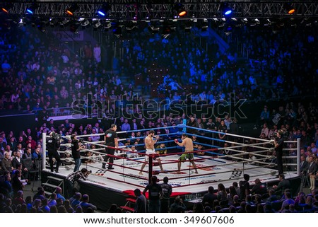 Chelyabinsk, Russia - December 5, 2015: General plan of sports arena during fight in ring, fighters and referee across ring fans during Cup of Russia MMA - stock photo