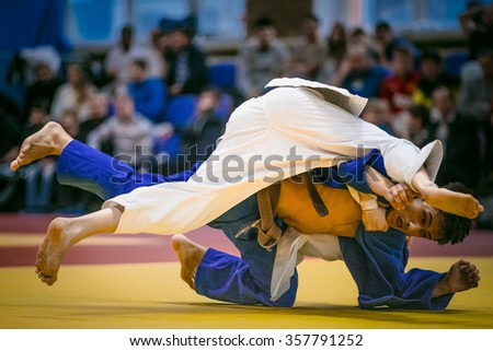 Chelyabinsk, Russia -  December 20, 2015: wrestling duel between athlete men judokas on tatami during All-Russian competition on judo of memory Grigory Verichev - stock photo