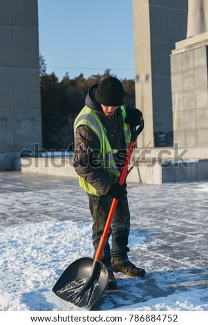 CHELYABINSK, RUSSIA, JANUARY 03, 2018: Workers sweep snow from road in winter. Cleaning road and street from snow and ice