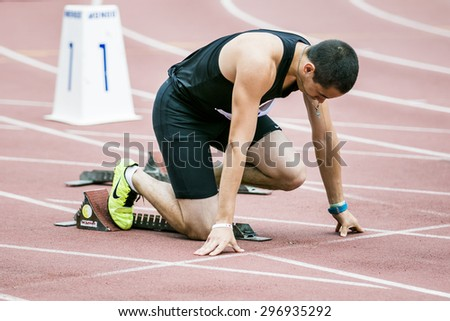 Chelyabinsk, Russia - July 05, 2015: Man athlete in starting position sprint race during Championship of Russia on track and field athletics among the blind - stock photo