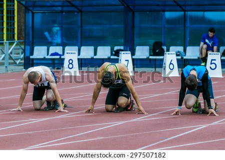 Chelyabinsk, Russia - July 10, 2015: sprinters on the start line 100 m during Championship of Chelyabinsk on track and field athletics, Chelyabinsk, Russia - July 10, 2015 - stock photo