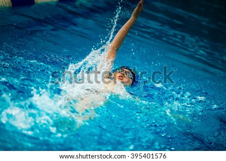 Chelyabinsk, Russia - March 18, 2016: young man athlete swimming backstroke in sprint distance in pool during International swimming tournament
