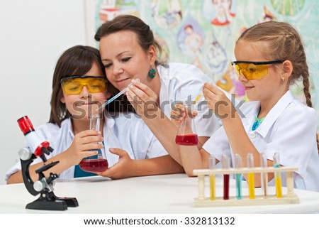 Chemical experiments in elementary school - kids helped by teacher in science class - stock photo