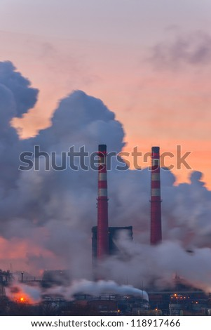 Chemical factory in the morning, with pipes and polluting smoke, long exposure - stock photo