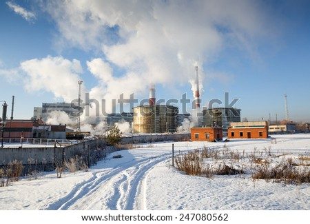 Chemical factory with smoke stack in winter - stock photo