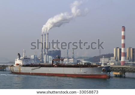 Chemical/power plant air pollutions with white clouds of smoke, crude oil tanker, disharging on front - stock photo