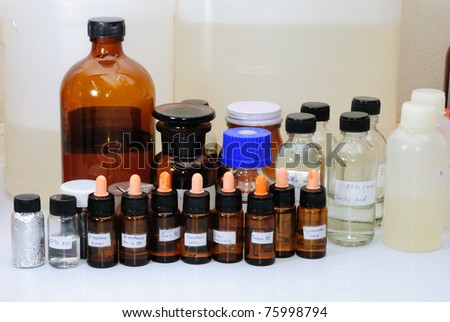 Chemical reactants in glass capacities stand on a regiment in chemical laboratory. Carrying out of scientific researches. - stock photo