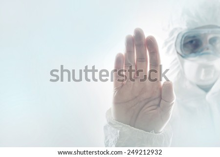 Chemical Scientist Gesturing Stop Sign with his Hand Raised in the Air, while wearing a protective clothing. Chemical disaster and pollution conceptual image with selective focus and shallow DOF. - stock photo