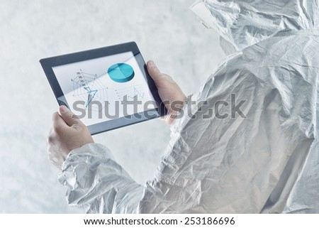 Chemical scientist using digital tablet computer with data infographics - stock photo