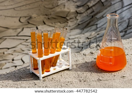 Chemical supplies, chemical analysis of the GMO destruction of the soil, the earth cracked orange liquid genetics study of lab - stock photo