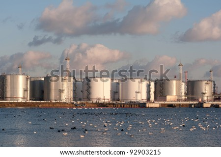 Chemical tank in port on the sunset with seagulls - stock photo