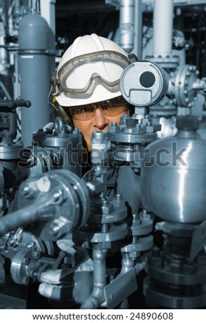 chemical worker behind large fuel pump machinery, blue toning concept - stock photo