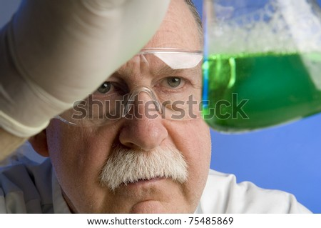 Chemist looking closely at his latest discovery - stock photo