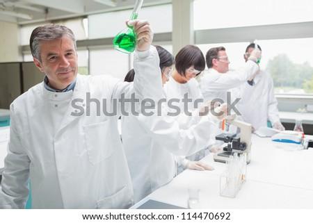 Chemist raising beaker of green liquid in busy lab - stock photo